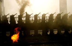 西安-2月2日。2007年2月2日,一名工人在西安焦化厂的炼焦炉上工作。 据西安的环保部门的消息,西安西郊工业集中区大气污染专项整治已经启动,期间将完成对西安焦化厂的关闭工作。西安焦化厂关闭后,将年削减3亿立方米废气,减排烟尘、粉尘1500吨。
